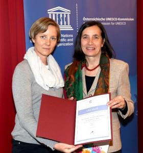 JGI-A Geschäftsführerin Mag.a Gudrun Schindler-Rainbauer (links) nimmt die UNESCO-Auszeichnung entgegen